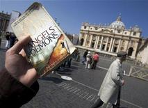 """<p>A guide with the """"Official Angels & Demons Tour"""" holds a copy of the book by Dan Brown while accompanying a group of American tourists retracing its plot at Saint Peter's square in the Vatican May 1, 2009. REUTERS/Chris Helgren</p>"""