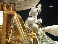 <p>Astronautas Good e Massimino trabalham no telescópio Hubble. 15/05/2009 REUTERS/NASA TV</p>