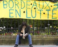 """<p>A French university student sits beneath a banner which reads """"Bordeaux III in dispute"""" during an outdoor class session in the centre of Bordeaux, southwestern France, May 19, 2009. French students continue their 16-week battle against a shake up of the university system. REUTERS/Olivier Pon</p>"""