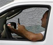 <p>A man uses a cell phone while driving in Burbank, California June 25, 2008. REUTERS/Fred Prouser</p>