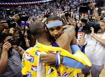 <p>Il cestista dei Los Angeles Lakers Kobe Bryant abbraccia il collega dei Denver Nuggets Carmelo Anthony dopo la vittoria in Nba. REUTERS/Mark Leffingwell</p>