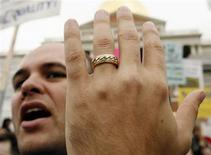 <p>Gay marriage supporter Josh Drew shows off his wedding ring outside the Massachusetts State House in Boston November 9, 2006. REUTERS/Brian Snyder</p>