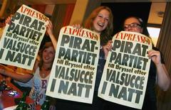 """<p>Supporters of Sweden's Pirate Party celebrate at an election night party as results from EU Parliamentary elections are announced in Stockholm June 7, 2009. The mock-up of a newspaper front page reads """"Pirate Party to Brussels after being chosen tonight"""". REUTERS/Bob Strong</p>"""