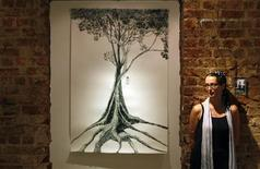 """<p>Singapore Artist Lucy Davis poses next to a work from her series """"Together Again (Wood: Cut)"""" at the Post-Gallery in Singapore May 18, 2009. REUTERS/Vivek Prakash</p>"""