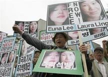<p>Демонстранты держат портреты журналисток Лауры Лин и Юны Ли на митинге в Сеуле 9 июня 2009 года. Родственники двух журналисток, приговоренных в КНДР к 12 годам каторжных работ за нелегальное пересечение границы, попросили Пхеньян сжалиться над осужденными, в то время как представитель администрации США заявил о невиновности задержанных, работавших на американский телеканал, и призвал освободить их. REUTERS/Lee Jae-Won</p>