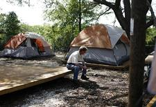 <p>Buddy sits outside his tent at the tent city homeless community, known as Pinellas Hope in Pinellas Park, Florida June 6, 2009. REUTERS/Carlos Barria</p>