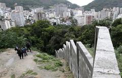 <p>Policemen patrol next to a wall being built by Rio de Janeiro city hall to limit the expansion of the Dona Marta slum from encroaching on the forest in Rio de Janeiro May 29, 2009.REUTERS/Sergio Moraes</p>