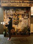 <p>Uma pedestre lê um jornal ao lado do memorial feito para o brasileiro Jean Charles de Menezes próximo à entrada do da estação de metrô Stockwell em Londres. 12/12/2008. REUTERS/Andrew Winning</p>