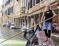 <p>The first certified female gondolier, Giorgia Boscolo, poses on a gondola after passing her exams in Venice June 26, 2009. Boscolo, 23, is a married mother of two children, and her father Dante is also a gondolier. REUTERS/Manuel Silvestri</p>