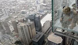 "<p>Five-year-old Anna Kane, of Alton, Illinois, looks through the glass floor of ""The Ledge"", 1,353 feet (412 meters) above the street in Chicago July 1, 2009. The Ledge is part of Skydeck Chicago located on the 103rd floor of the Sears Tower. It opens to the public July 2. REUTERS/Frank Polich</p>"