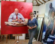<p>British artist Claire Phillips stands by her oil paintings of death row inmates, in this 2009 handout photo. REUTERS/Michael Phillips/Handout</p>