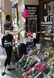<p>Uma menina amarra um balão na frente do Lyric Theatre, onde havaerá uma performance para a música de Michael Jackson, em Londres. 05/07/2009. REUTERS/Luke MacGregor</p>