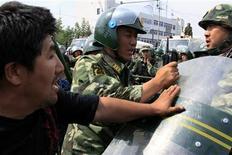 <p>Poliziotti e civili durante gli scontri nel Xinjiang. REUTERS/David Gray</p>