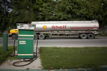 A Shell fuel tanker passes by a local gas station in Haina June 16, 2009. REUTERS/Eduardo Munoz