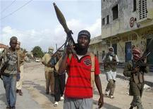 <p>Боевики-исламисты патрулируют улицы Могадишо 2 июля 2009 года. Несколько вооруженных людей взяли штурмом гостиницу в столице Сомали Могадишо и захватили в заложники двух французских журналистов во вторник, сообщили сотрудник отеля. REUTERS/Mowliid Abdi</p>