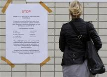 <p>A woman reads a H1N1 flu virus warning sign outside a hospital in London, July 22, 2009. REUTERS/Toby Melville</p>