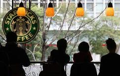 <p>Customers sit inside a branch of Starbucks in the Jimbocho district of Tokyo March 15, 2007. REUTERS/Kevin Coombs</p>