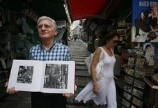 """<p>Edward Stokes, fundador de la Fundación del Patrimonio Fotográfico de Hong Kong, posa con el libro """"Hong Kong as It Was"""" con fotografías tomadas por Hedda Morrison entre 1946 y 1947, en Hong Kong, 10 jul 2009. El escritor y fotógrafo Edward Stokes estableció la Fundación del Patrimonio Fotográfico de Hong Kong en el 2008 para desenterrar, contextualizar y publicar tales imágenes. La primera publicación de la organización, """"Hong Kong As It Was"""", ofrece asombrosas imágenes en blanco y negro tomadas por la fotógrafa alemana Hedda Morrison y que representan la vida cotidiana de la década de 1940. REUTERS/Bobby Yip</p>"""