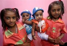 <p>Seven-year-old Fathima Lubna (L) and her twin sister Fathima Lubaba (R) carry their five-month-old sisters, who are also twins, at their residence in Kodinji village in the southern Indian city of Kerala July 28, 2009. REUTERS/Arko Datta</p>