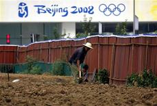 <p>A Chinese worker excavates an area in front of the National Aquatics Centre, also known as the Water Cube, in Beijing August 6, 2009. REUTERS/David Gray</p>
