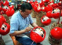 <p>A Japanese craftsman adds the final touches to a daruma doll in Takasaki. REUTERS/file</p>