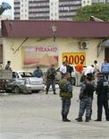 """<p>Милиционеры изучают место взрыва на улице Грозного 21 августа 2009 года. Как минимум четыре человека погибли в столице Чечни в пятницу в результате серии взрывов, ответственность за которые Следственный комитет прокуратуры возложил на """"террористов- смертников"""", передвигавшихся на велосипедах. REUTERS/Khamzad Ibragimov</p>"""