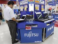 <p>Foto de archivo de un hombre frente a una computadora portátil de Fujitsu en una tienda en Tokio, 30 jul 2009. Fujitsu Ltd, la mayor firma de servicios de tecnología de la información de Japón, casi cuadruplicó su previsión anual de ganancias luego de que vendiera una participación en el fabricante de robots industriales Fanuc Ltd por 89.000 millones de yenes (945 millones de dólares). REUTERS/Yuriko Nakao</p>