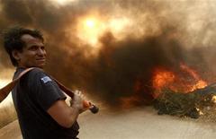 <p>Пожарный готовится к новой битве с огнем, который охватил лес в деревне Грамматико, недалеко от Афин 22 августа 2009 года. Греческие пожарные бригады заставили отступить лесные пожары, которые три дня бушевали около Афин и угрожали столице Греции, заставляя людей покидать свои жилища, сообщили власти. REUTERS/Yiorgos Karahalis</p>