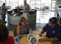 """<p>Erlinda Sandoval goes over paperwork for her 1998 Dodge Caravan trade-in with salesman Blake Greenberg (R) during the last day of the """"cash-for-clunkers"""" auto rebate program at the Courtesy Chevrolet dealership in Phoenix, Arizona, August 24, 2009. REUTERS/Joshua Lott</p>"""