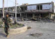 <p>Афганский солдат у места взрыва в Кандагаре 26 августа 2009 года. Серия взрывов автомобилей в афганском Кандагаре унесла жизни 40 человек, еще 60 были ранены на фоне подсчета голосов на президентских выборах, обостривших борьбу двух основных кандидатов на пост главы страны. REUTERS/Ahmad Nadeem</p>