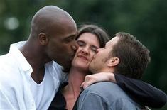 <p>The winner of British TV company Channel 4's 'Big Brother' gameshow Craig Phillips (R) plants a kiss with fellow contestant Darren Ramsey (L) on Anna Nolan's cheek (2R) on the set of the TV show September 16, 2000. REUTERS/Dan Chung</p>