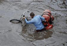 <p>Un vendedor traslada cilindros de gas por una calle inundada en la ciudad india de Mathura, 26 ago 2009. La adaptación a los efectos del cambio climático, como inundaciones y sequías, probablemente costará dos o tres veces más de lo que estiman las Naciones Unidas, dijo el jueves un informe previo a la cumbre de la ONU en diciembre. REUTERS/K. K. Arora</p>