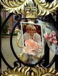 <p>Портрет принцессы Дианы на воротах Кенсингтонского дворца в Лондоне 25 августа 1998 года. 31 августа 1997 года британская принцесса Диана и ее друг Доди аль-Файед погибли в автокатастрофе в Париже. REUTERS/Kevin Lamarque</p>