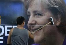 <p>Un trabajador pega un cartel con el rostro de la canciller germana, Angela Merkel, de cara a las elecciones generales en Dortmund, Alemania, 31 ago 2009. Las autoridades electorales alemanas dijeron el lunes que están investigando si sondeos a boca de urna se publicaron en Twitter antes del cierre de los colegios electorales y que podría haber una apelación sobre el resultado en el caso de que se hubiera infringido la ley. REUTERS/Ina Fassbender</p>