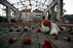 <p>Мягкая игрушка лежит среди цветов в сожженной гимназии номер 1 в Беслане 1 сентября 2007 года. REUTERS/Eduard Korniyenko</p>
