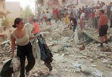 <p>Жительница Афин забирает одежду из разрушенного дома 7 сентября 1999 года, когда в городе в результате сильнейшего землетрясения погибли 139 человек. REUTERS/Stringer</p>
