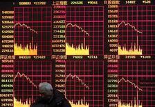 <p>Мужчина смотрит на электронное табло на бирже в Шанхае 24 февраля 2009 года. Россия стала единственной из стран БРИК, потерявшей позиции в общемировом рейтинге конкурентоспособности за 2009/2010 годы, опубликованном во вторник Всемирным экономическим форумом (ВЭФ). REUTERS/Aly Song</p>