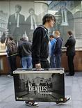 """<p>Un hombre camina frente de una tienda de HMV luego de comprar el juego """"The Beatles: Rock Band"""" en Liverpool, en el norte de Inglaterra, 9 sep 2009. Fans de la banda británica The Beatles salieron a las calles de Gran Bretaña el miércoles a comprar los nuevos discos recopilatorios del grupo con sonido remasterizado y conseguir un videojuego que se espera capture a una nueva generación de seguidores. La colección de los """"fabulosos cuatro"""", presentada en todo el mundo el 09/09/09 y cuyo precio es de 300 dólares, probablemente encabezará las ventas en mercados como Estados Unidos y Reino Unido, lo que supondría un impulso para la discográfica EMI Music y la empresa de los Beatles Apple Corps. Mientras crecían las filas en las principales tiendas de música de Londres, también se sumaban nostálgicos en otras partes de Europa y Asia. REUTERS/Darren Staples</p>"""