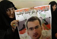 <p>Una parente del giornalista iracheno Muntazer al-Zaidi con in mano un'immagine dell'uomo. REUTERS/Thaier al-Sudani</p>