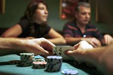 <p>A player checks his cards during a poker game at a Budapest casino in Budapest September 15, 2009. REUTERS/Katoly Arvai</p>