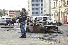 <p>Сотрудник правоохранительных органов стоит рядом с остовом машины, сгоревшей в результате взрыва смертницы в Грозном 16 сентября 2009 года.Взрыв смертницы в оживленном районе Грозного ранил двух сотрудников милиции и четверых прохожих утром в среду, сообщил журналистам глава МВД Чечни Руслан Алханов. REUTERS/S.Dal</p>