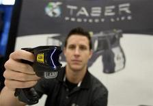 <p>Brian Black of Taser International demonstrates their X26 model at a trade show for the Canadian Association of Chiefs of Police in Montreal August 26, 2008. REUTERS/Christinne Muschi</p>