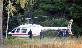 <p>Полицейские осматривают вертолет, использованный грабителями для налета на склад и брошенный в пригороде Стокгольма 23 сентября 2009 года. Вооруженные грабители в среду использовали вертолет для нападения на охраняемый склад на окраине столицы Швеции. REUTERS/Scanpix/Maja Suslin</p>