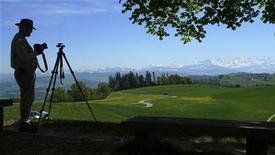 <p>A photographer prepares to take pictures of Switzerland's Alps from the top of Gurten mountain in Bern May 7, 2009. REUTERS/Petr Josek</p>