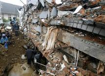 <p>Солдат и несколько добровольцев ищут жертв землетрясения под завалами в индонезийском Паданге 1 октября 2009 года. Спасатели под проливным дождем ищут людей под обломками зданий, разрушенных сильным землетрясением в индонезийском городе Паданг; число жертв стихии может составить тысячи. REUTERS/Crack Palinggi</p>