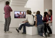 """<p>People watch the short film """"A sunset takes 7 minutes"""" by Johanna Domke during the Art between Traces of the Past and Utopian Futures exhibition in the Berlinische Gallerie in Berlin September 30, 2009. REUTERS/Thomas Peter</p>"""