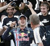 <p>Il tedesco Sebastian Vettel festeggia con i compagni della Red Bull la vittoria in Giappone. REUTERS/Issei Kato</p>