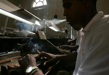 <p>A cigar roller smokes a cigar while working at Havana's Cohiba factory in this March 2, 2006 file photo. Cash-short Cuba is slashing the amount of land devoted to production of its famous tobacco by more than 30 percent as the global recession and the worldwide spread of smoking bans bite into sales of the country's prized cigars. REUTERS/Claudia Daut/Files</p>