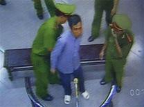 <p>Immagine del professore Vu Hung ammanettato dalla polizia di Hanoi. REUTERS/Kham</p>