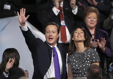 Conservative Party leader, David Cameron, waves as he stands among delegates, with his wife Samantha, after delivering his keynote address at the party conference in Manchester, October 8, 2009. REUTERS/Andrew Winning